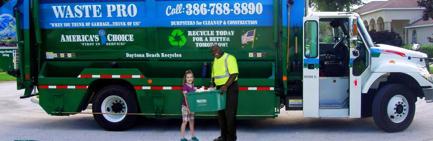 A photo of a Waste Pro truck with an employee and a child in front of the truck